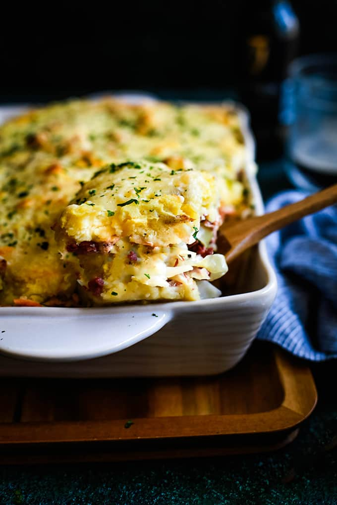 A square of casserole, with chopped parsley and melted cheese, being lifted out of a baking dish.