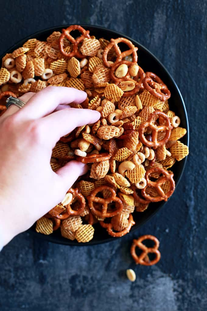 A bowl of chex mix with a hand grabbing a handful