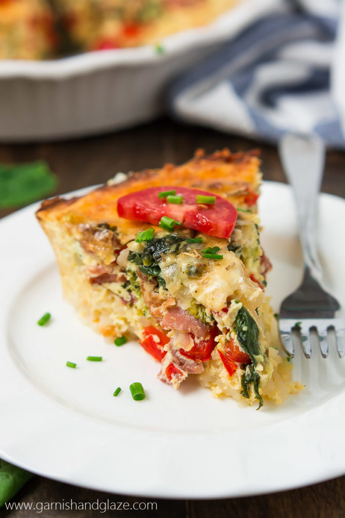 a wedge of quiche with spinach and tomatoes
