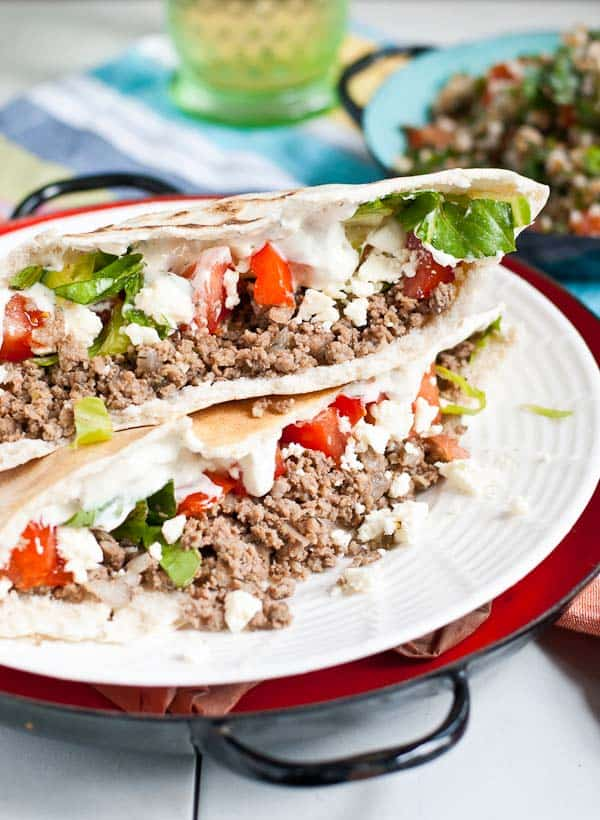 A ground beef stuffed gyro topped with shredded lettuce, diced tomatoes, and tzatziki sauce