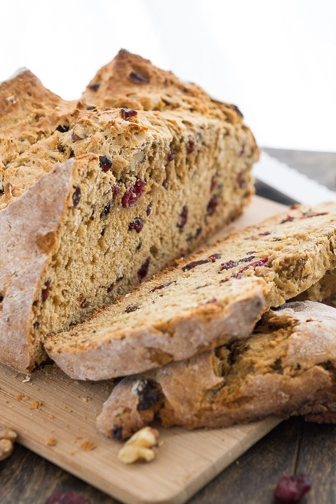 Slices off a loaf of irish soda bread, with cranberries and walnuts