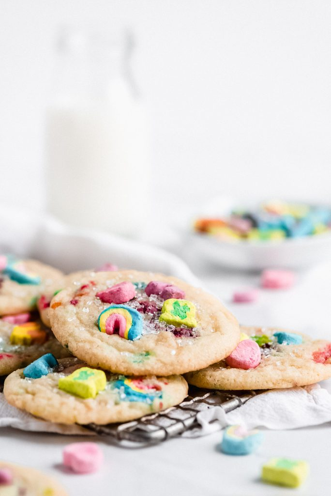 a pile of cookies with lucky charms marshmallows in them on a wire cooking rack