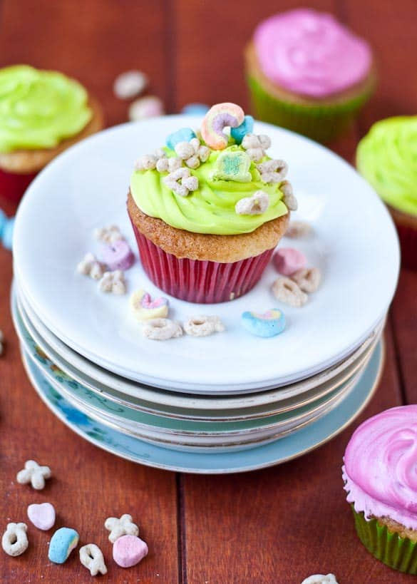 a cupcake with green frosting and lucky charms on it on a stack of plates