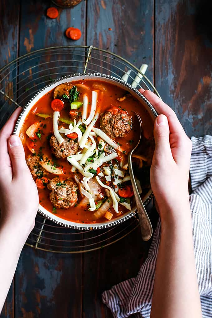 a hand holding a bowl of soup with meatballs, grated mozzarella cheese, vegetables, and spoon
