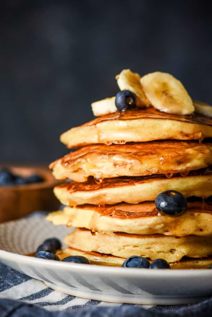 a stack of pancakes with blueberries and bananas on top