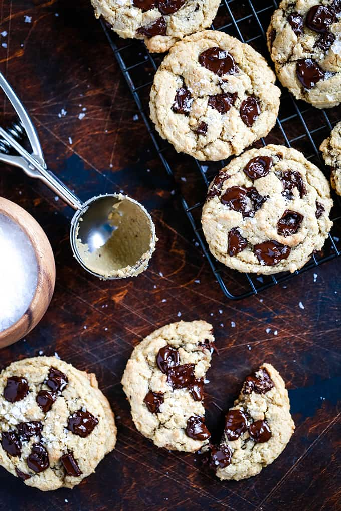a wooden board with chocolate chip cookies, a cookie scoop and a dish of kosher salt