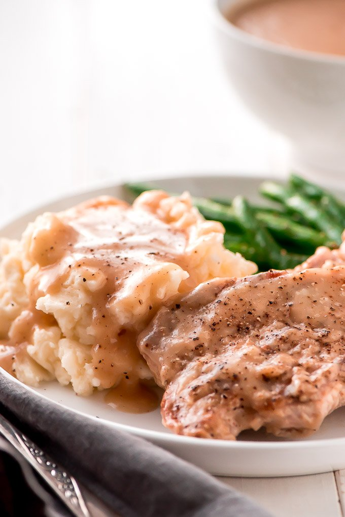 A plate with pork chops and mashed potatoes, both smothered in gravy, with a side of green beans
