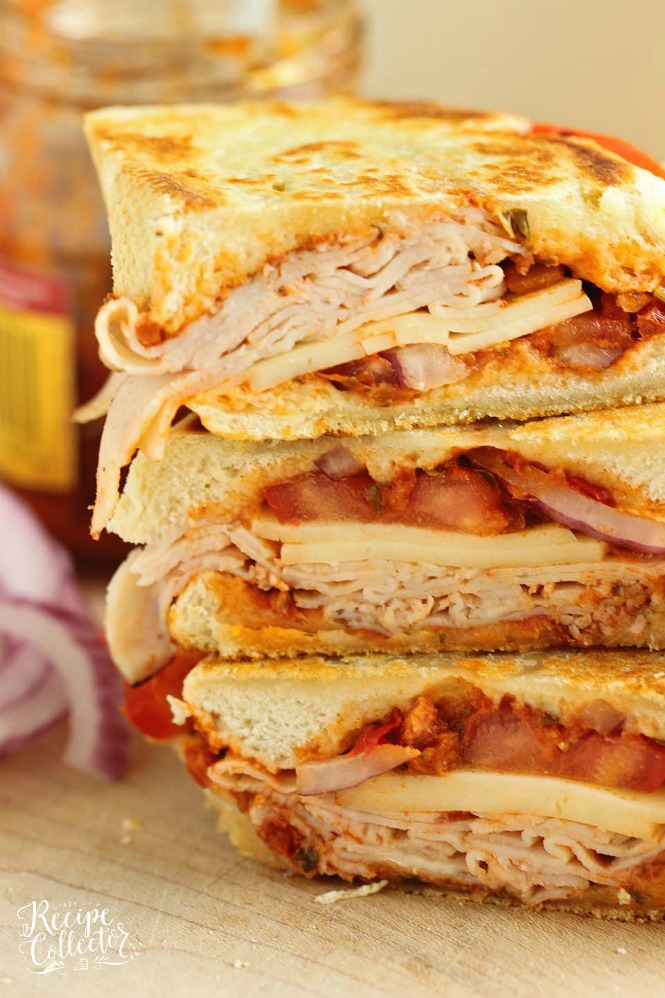 A stack of turkey and cheese panini's cut in half