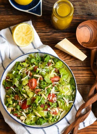 a green salad with parmesan cheese, bacon, and chopped tomatoes