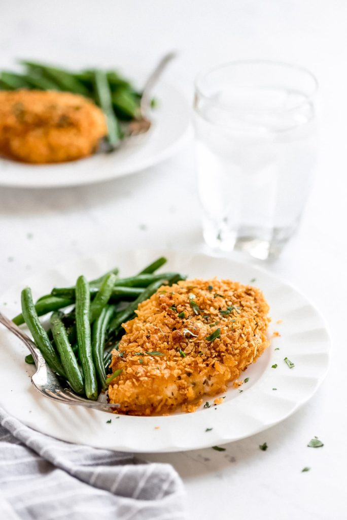 a baked, cornflake coated chicken breast and green beans on a plate