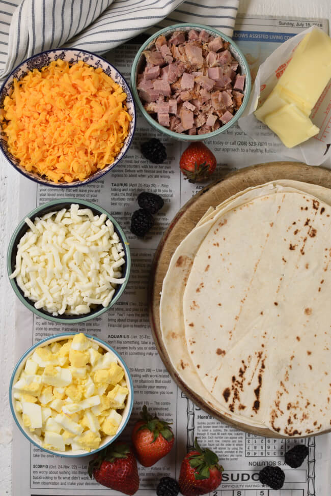 bowls with ham, cheese, eggs, and tortillas