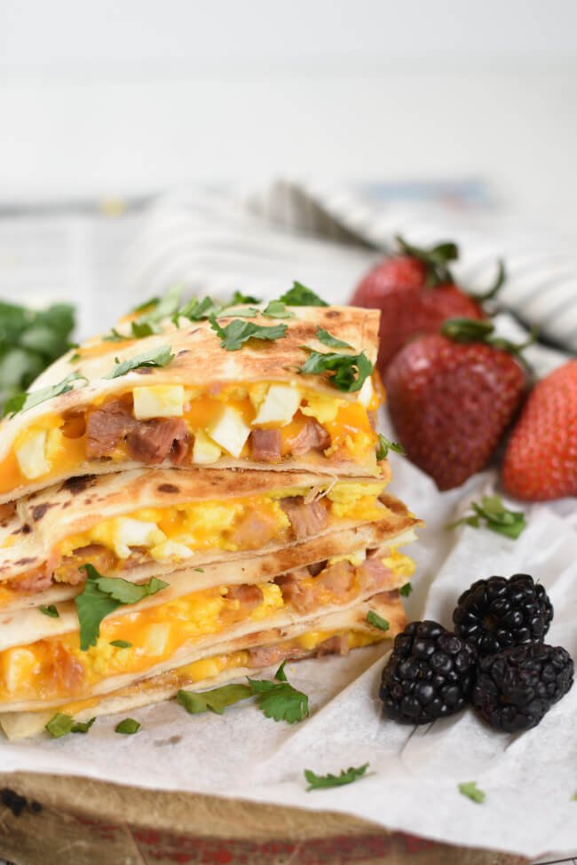a stack of quesadilla wedges with strawberries and blackberries