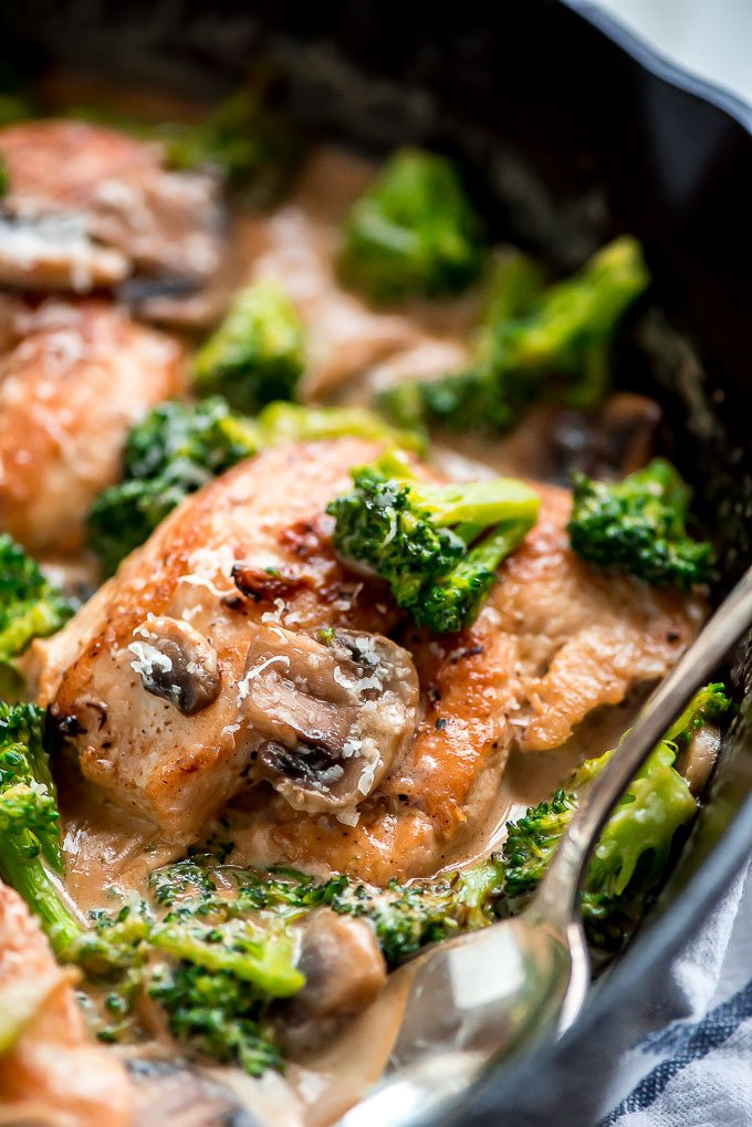 a cast iron skillet with fried chicken smothered in broccoli and mushrooms