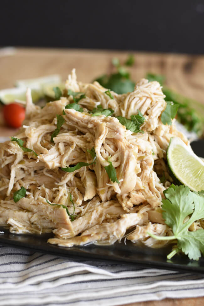 A platter with cooked and shredded chicken topped with chopped cilantro