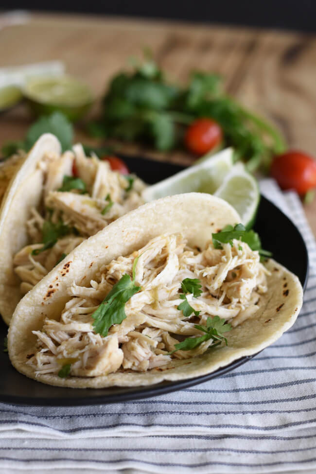 a shredded chicken taco with cilantro on a black plate