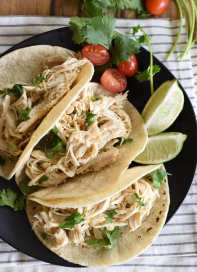 birds eye view of three shredded chicken tacos with lime wedges and cilantro