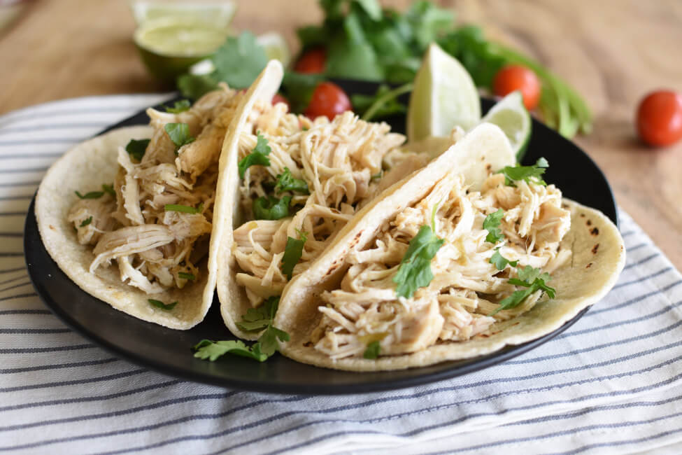 Three verde chicken tacos on a black plate