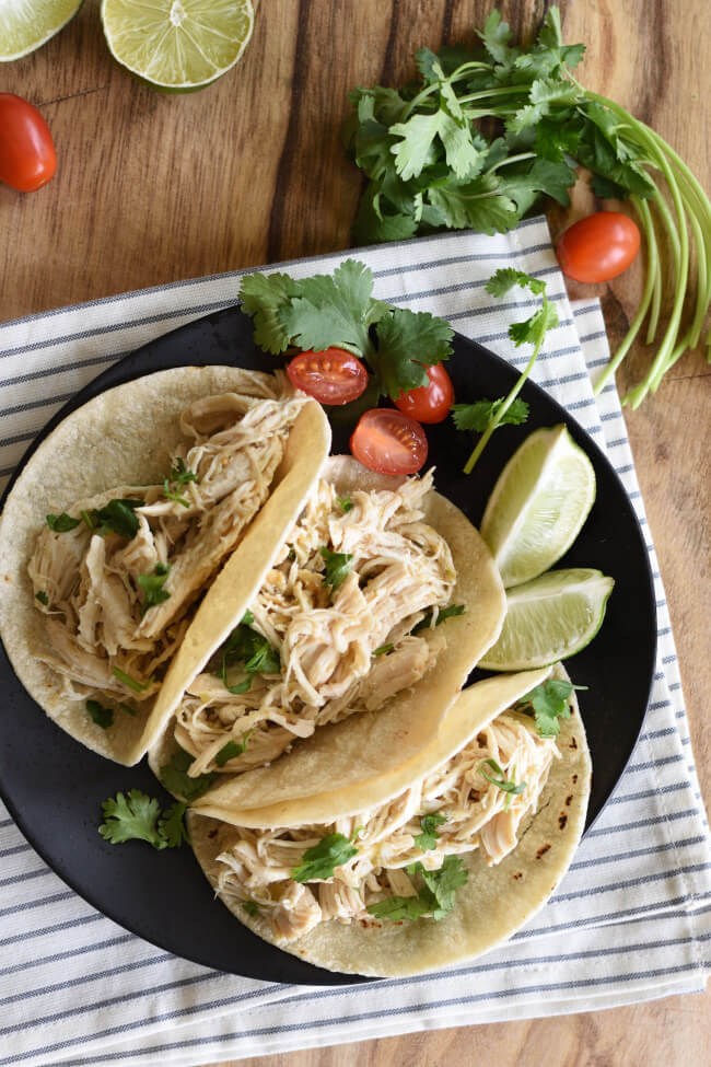 corn shell tacos filled with shredded chicken served with lime wedges and cherry tomato halves