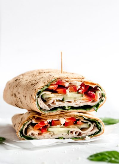a turkey wrap cut in half filled with red peppers and spinach