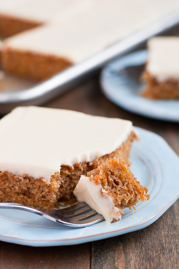 A plate with a square of carrot cake with white icing