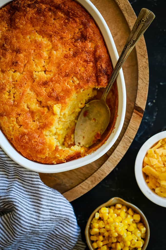 A white dish with golden brown corn casserole with a spoonful missing