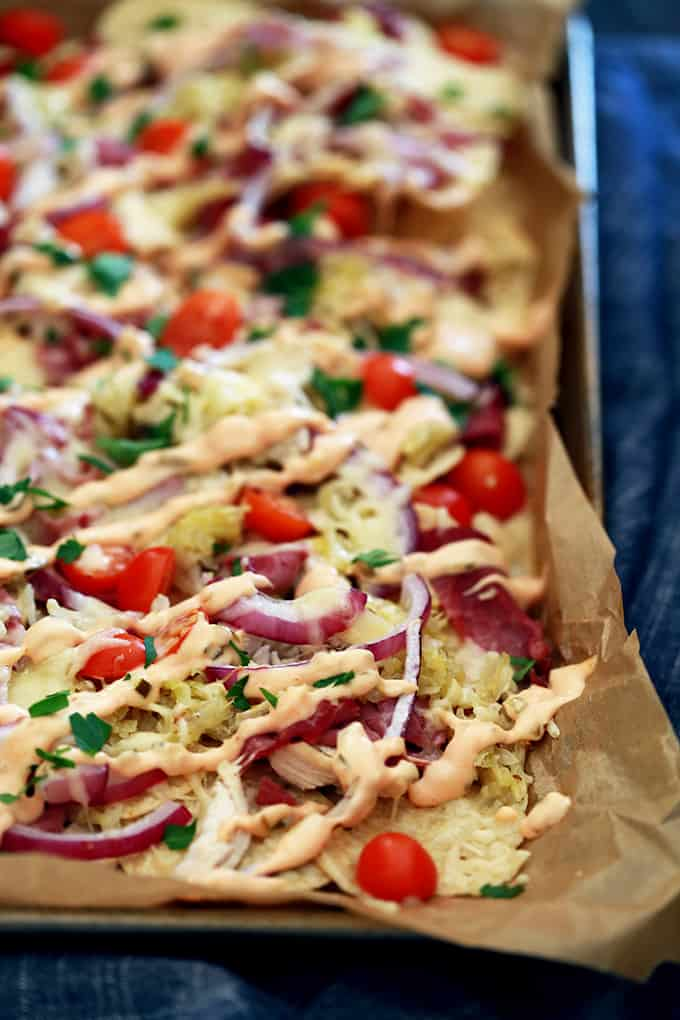a sheet pan of nachos with chicken, purple onions, tomatoes, and cilantro