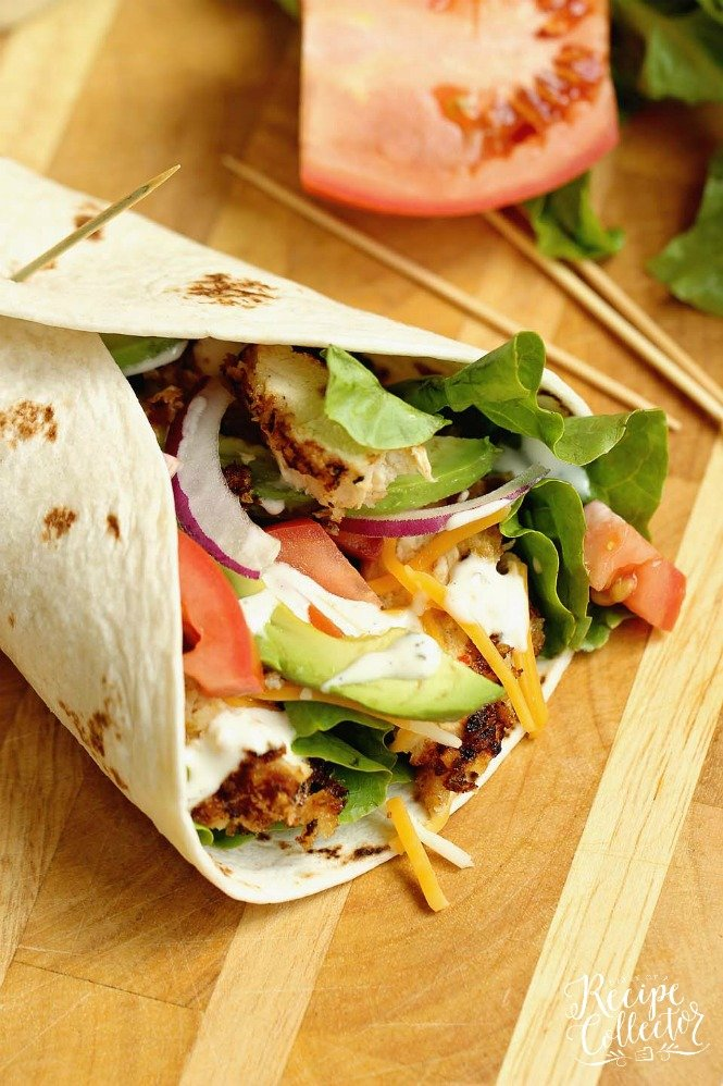 a flour tortilla wrap with chicken topped with avodados, lettuce, and tomatoes