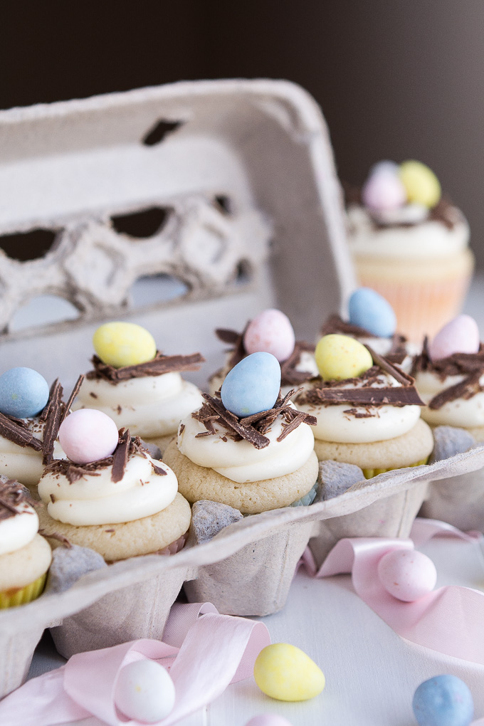 an egg carton with vanilla cupcakes decorated with chocolate eggs