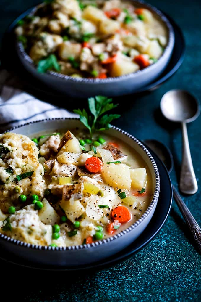 two bowls of chicken and dumplings soup with peas, carrots, and parsley
