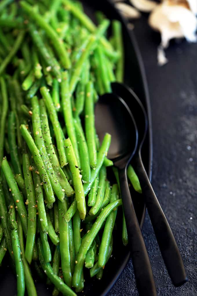 A black serving dish with cooked green beans