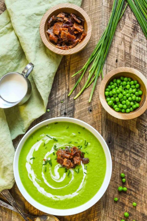 A bowl of bright green soup on a wooden board