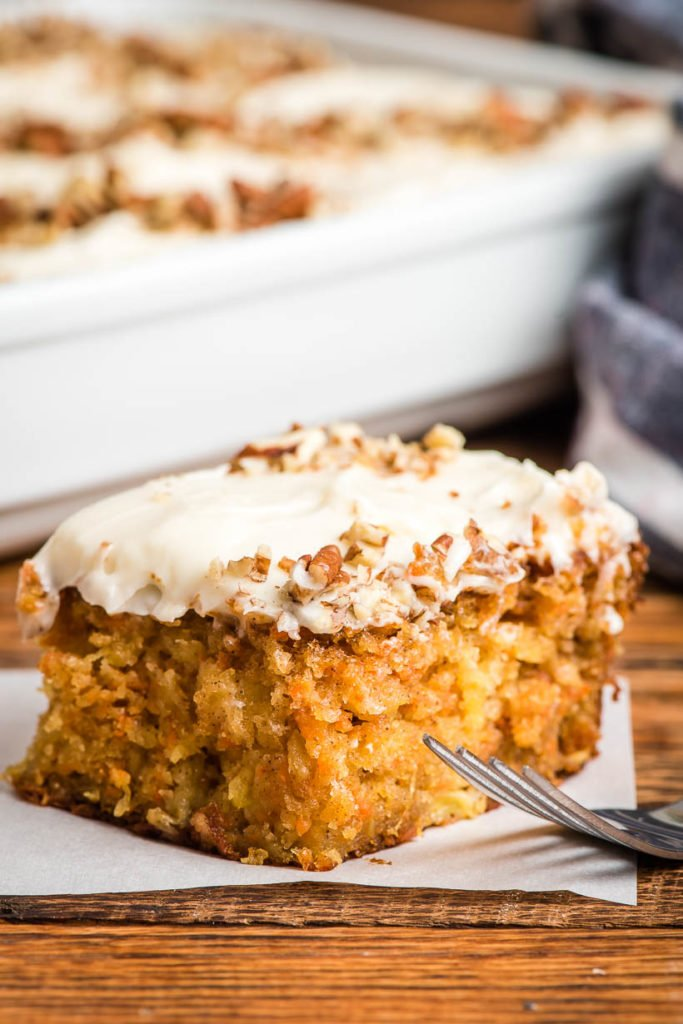 a square of carrot cake with cream cheese icing and chopped walnuts