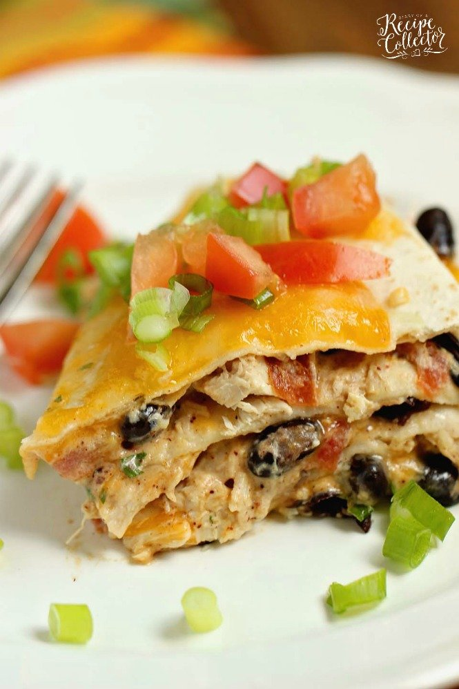 tortilas stacked and layered with beans and chicken, cut in a wedge and topped with onions and tomatoes