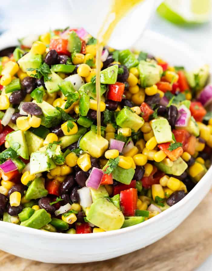 a white bowl with fresh diced tomatoes, avocados, corn, cilantro, and Italian dressing being drizzled over it