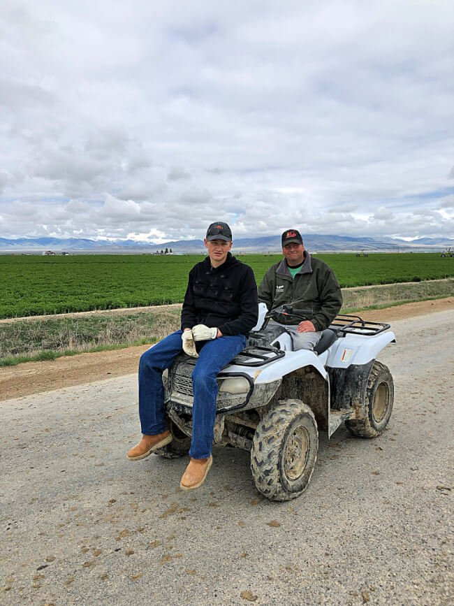 a man and a boy on a white four wheeler ATV