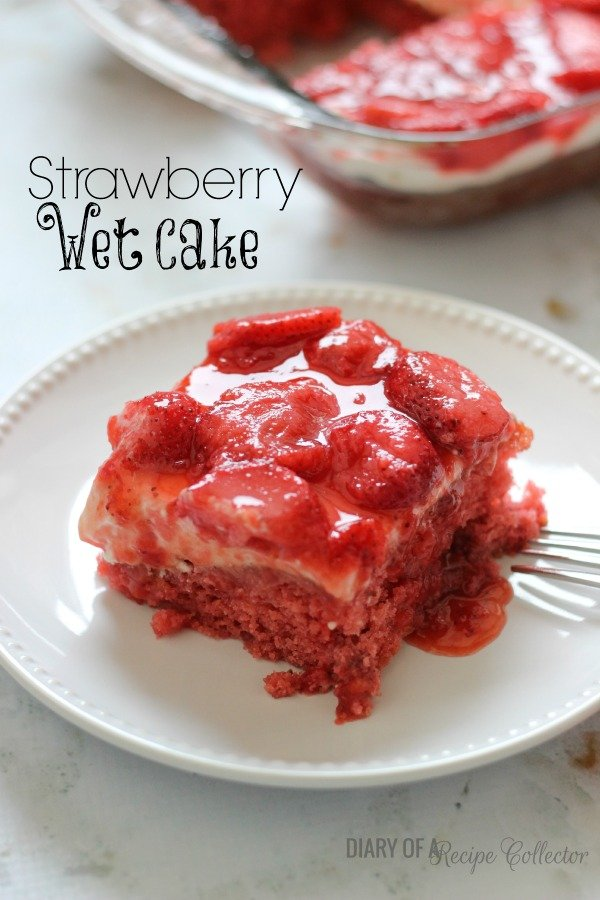 a square of red cake topped with whipped cream and strawberries in a glaze