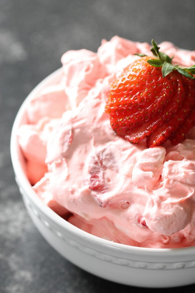 a white bowl with strawberry fluff salad topped with fresh strawberry