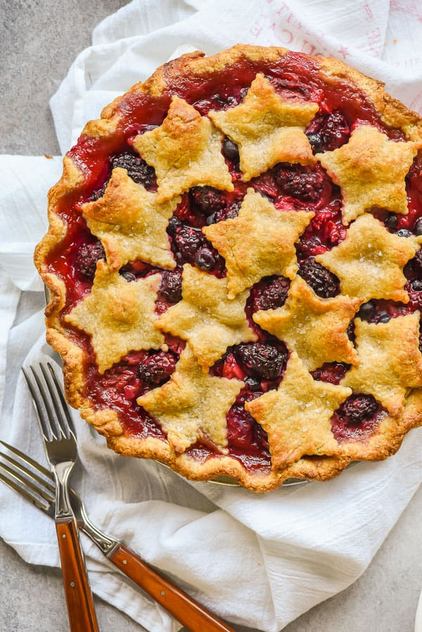 a baked berry pie topped with star shaped pie crust cookies