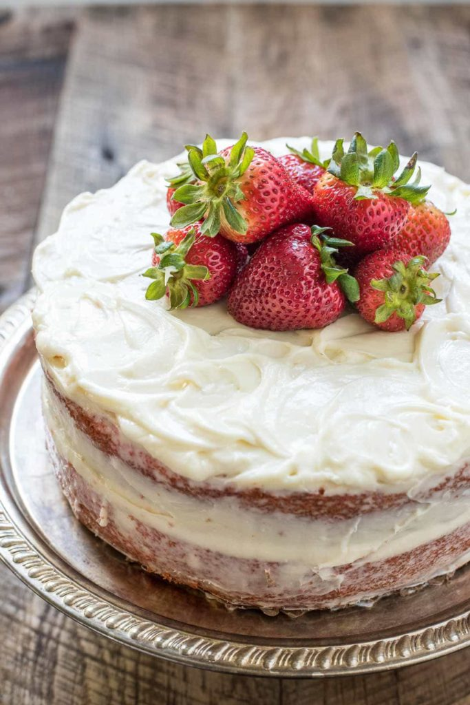 a two layer cake topped with cream cheese icing and fresh strawberries
