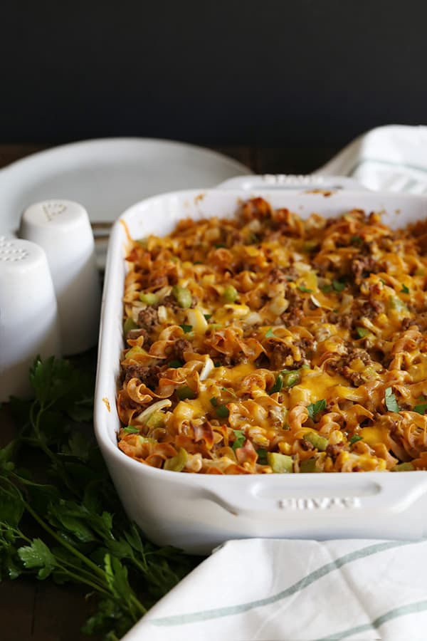 a white casserole dish with baked pasta that has hamburger, green onions, and cheese