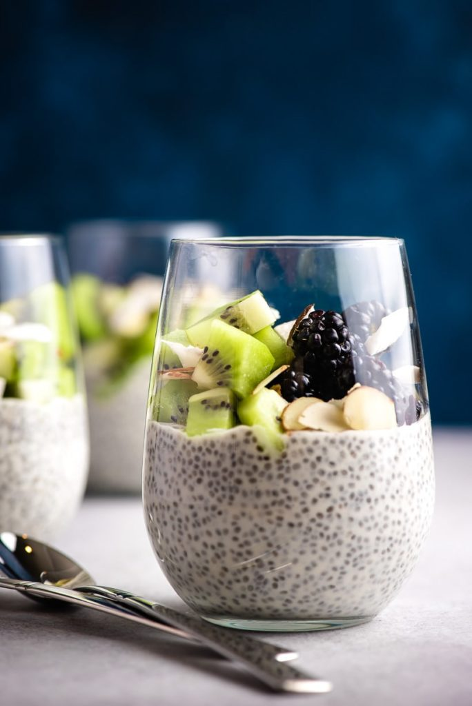 a short glass with chia pudding topped with chopped kiwi, blackberries, and sliced almonds