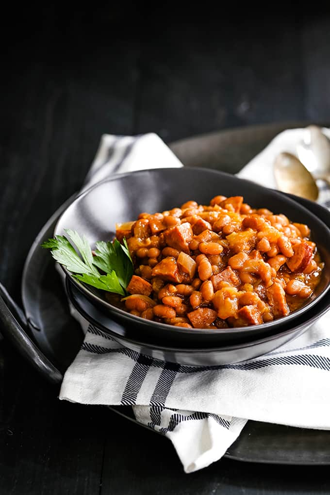 a black bowl with baked beans and a parsley lear on a white and black napkin