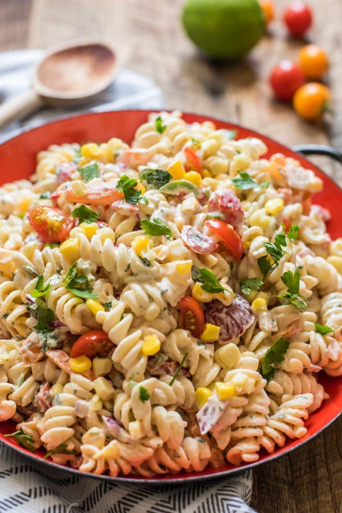 a red bowl with pasta salad with tomatoes, corn, and parsley