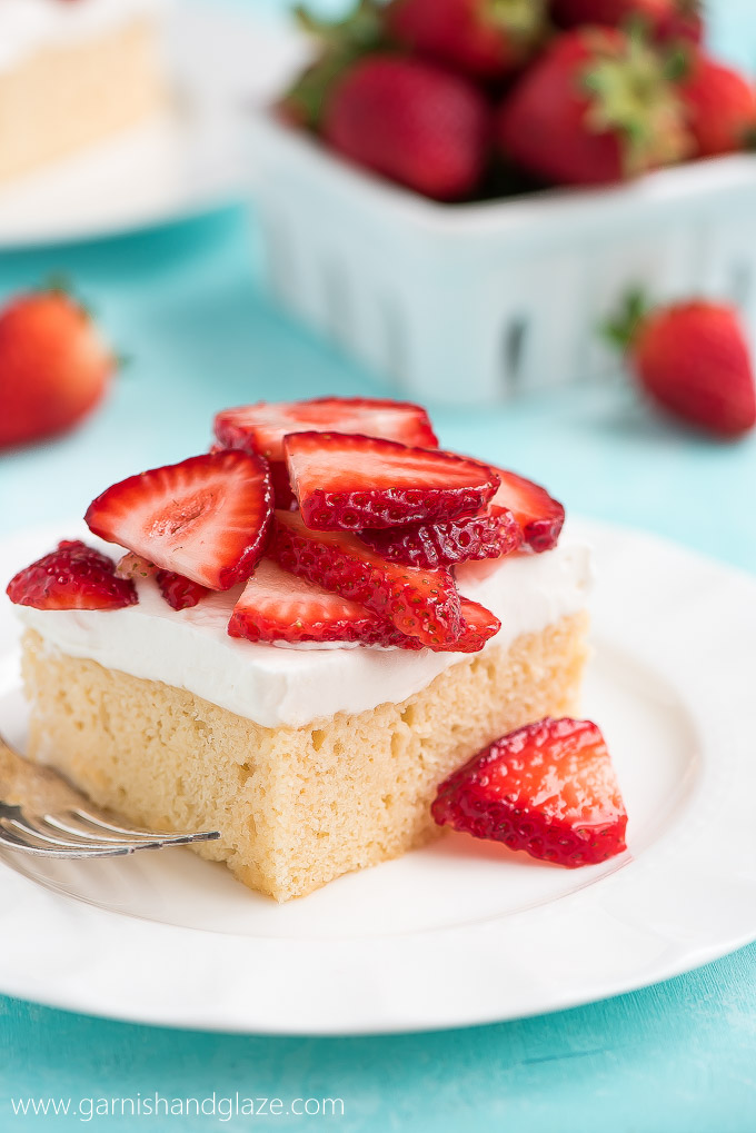 a square of white cake topped with sliced fresh strawberries