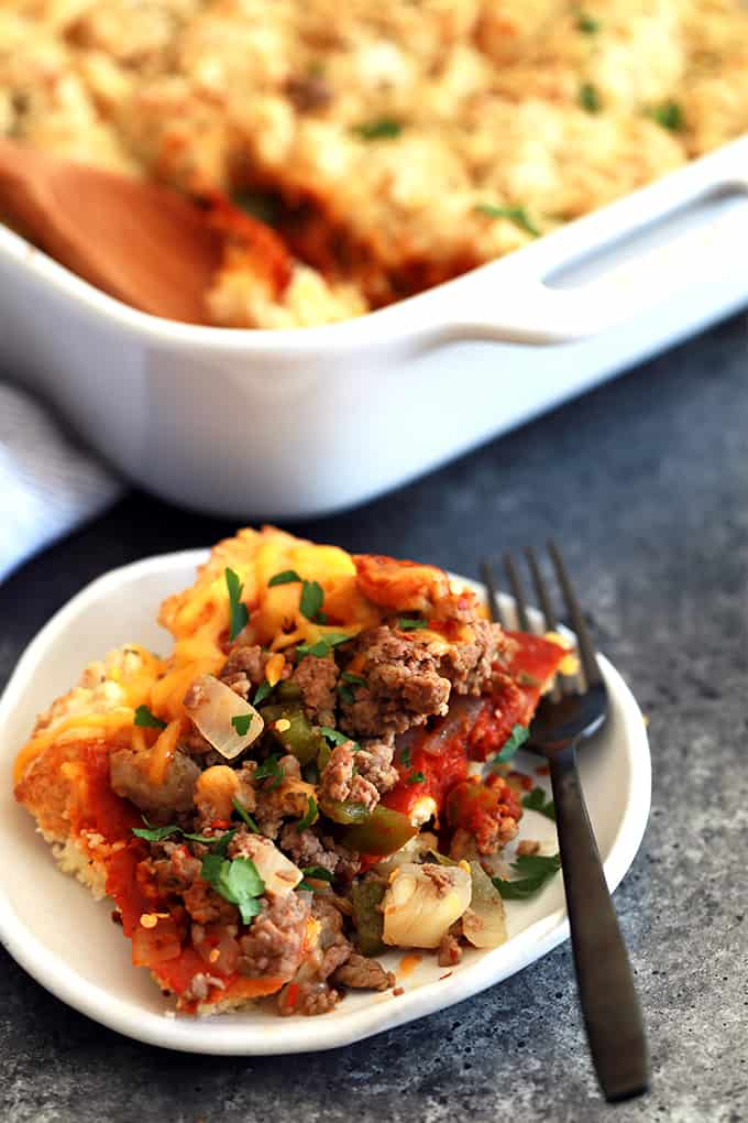 a white plate with baked casserole with onions, hamburger, cheese, tomatoes, and parsley. Two forks on the side