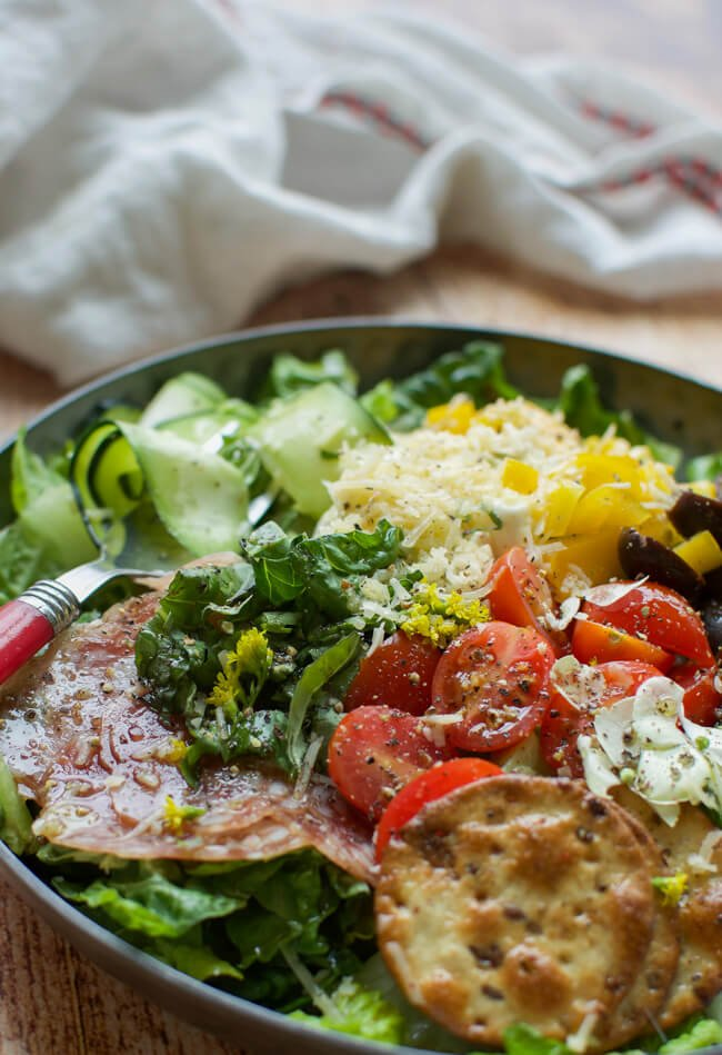 a shallow black bowl filled with salad made with peppers, tomatoes, olives, cheese, crackers, and salami