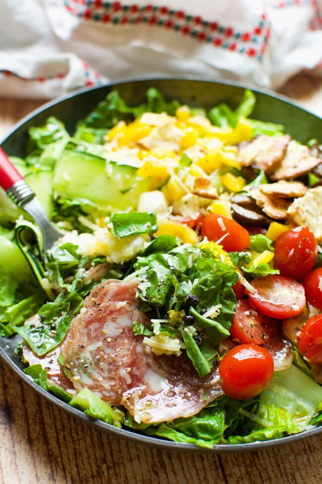 Green salad with tomatoes, olives, salami, and yellow peppers