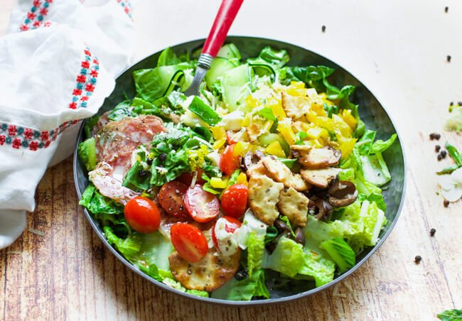a green salad with lots of toppings in on a black plate