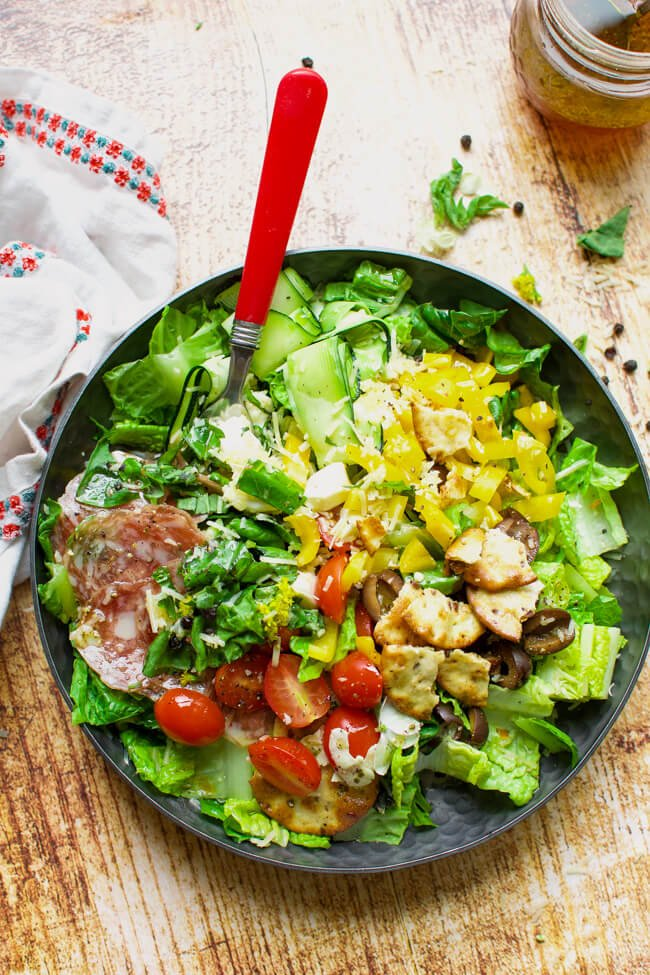 a black bowl with lettuce, olives, tomatoes, and salami