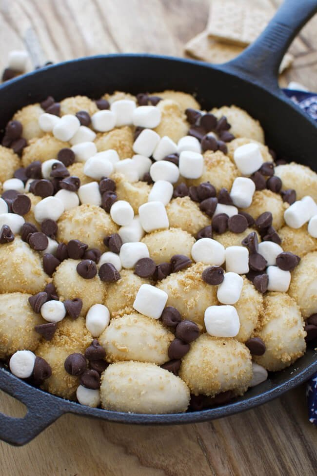 cast iron skillet with monkey bread topped with marshmallows and chocolate chips
